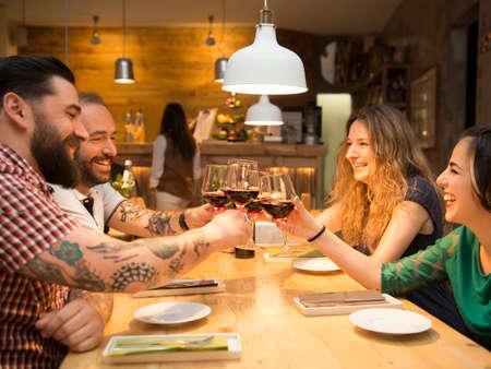 Gruppo di amici brindando e avere un buon tempo al ristorante