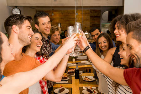 party food: Group of friends toasting and looking happy at a restaurant Stock Photo