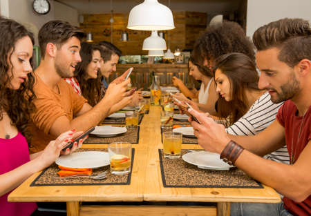 Gruppo di amici in un ristorante con tutte le persone sul tavolo occupato con i cellulari