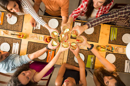 celebrate: Group of people toasting and looking happy at a restaurant Stock Photo