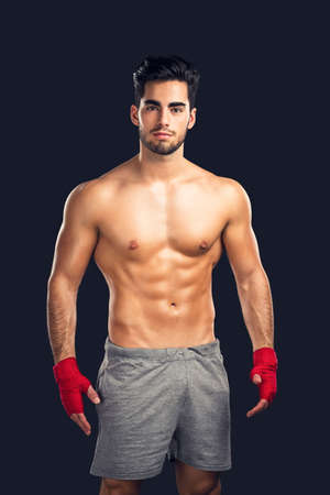 muscular man: Portrait of a young male Body Combat atlhlete, isolated over a dark background Stock Photo