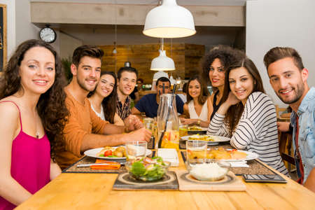 Gruppo multietnico di amici felici pranzare e divertirsi presso il ristorante