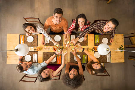 people eating restaurant: Group of people toasting and looking happy at a restaurant Stock Photo