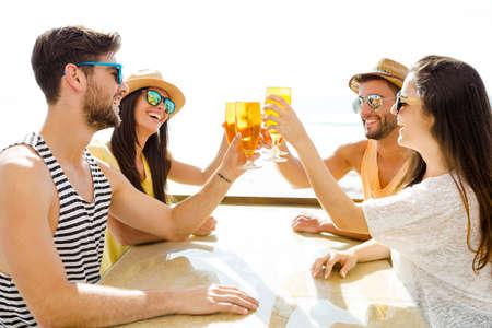 hombre tomando cerveza: Amigos que se divierten y beber una cerveza fría en el bar de la playa