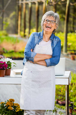 smiling woman in a greenhouse: Beautiful mature woman working in a greenhouse, looking at camera and smiling Stock Photo