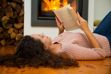 Bella donna che legge un libro al calore del camino