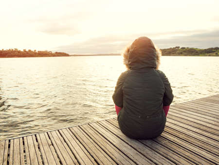 woman alone: Back view of a woman sitting close to a lake Stock Photo