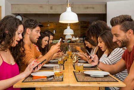 Groep vrienden in een restaurant met alle mensen op de tafel bezet met mobiele telefoons Stockfoto