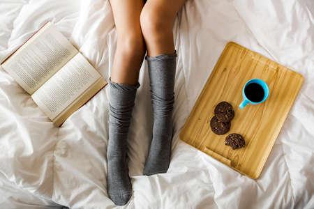 Frau auf dem Bett einen Kaffee mit Plätzchen trinkt Standard-Bild