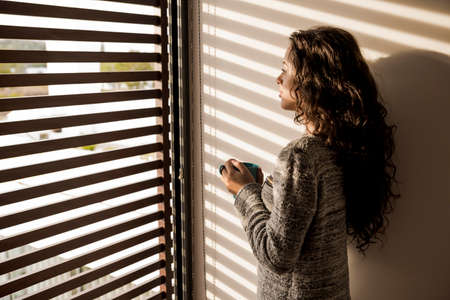woman window: Beautiful woman looking through a window and drinking coffee