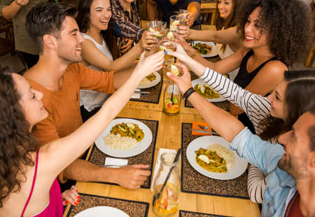 lunch table: Group of friends toasting and looking happy at a restaurant Stock Photo