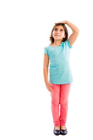 Kleines Mädchen, das oben schaut und die Kontrolle ihrer Größe