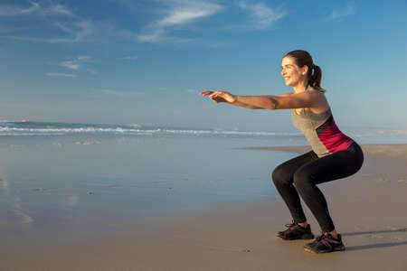 Shoot of a beautiful woman making squats exercises in the beach
