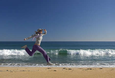 Young woman jumping for fun in a beautiful beach