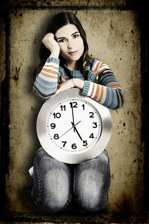 vintagel: Beautiful women over knees holding a big clock with a grunge background on the back (manilpulated in PS) Stock Photo