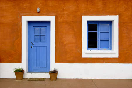 old house facade house: Beautiful and funny orange house with blue doors and windows Stock Photo
