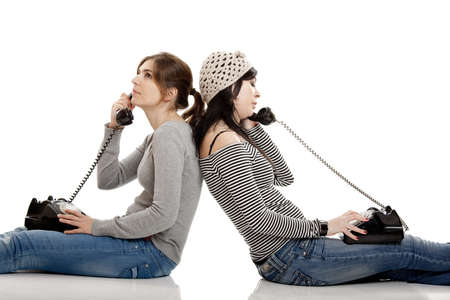 women talking: Two young women talking with old telephones - Isolated on white