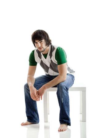 hombre sentado: Retrato de hombre joven sentado en un fondo blanco