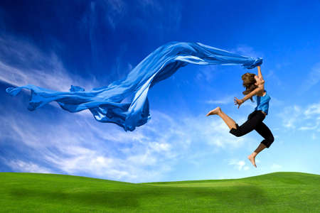 Beautiful athletic woman jumping on a green meadow with a scarf Stock Photo