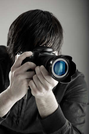 taking photograph: Young man holding a professional DSLR camera and taking pictures Stock Photo
