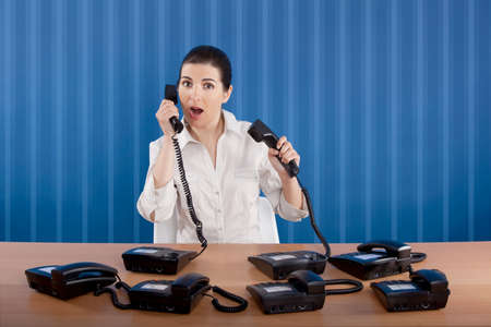 answering: Businesswoman answering a lot of calls at the same time
