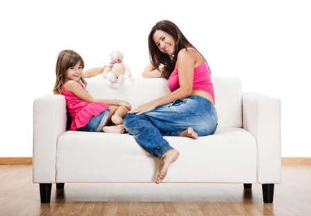 pregnant relaxing on sofa: Beautiful pregnant mother with her daughter isolated on white  Stock Photo