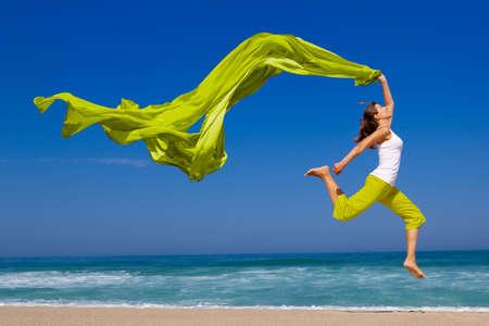 shawl: Prachtige jonge vrouw springen op het strand met een gekleurde weefsel Stockfoto