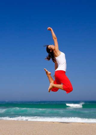 persona saltando: Hermosa mujer joven saltando en la playa