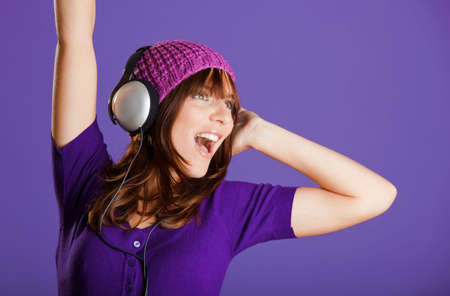 listen music: Beautiful and happy young woman listen music with headphones, over a violet background