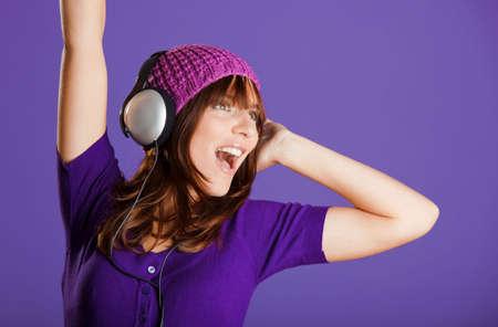 �couter: Heureuse et belle jeune femme �coutez la musique avec un casque, sur un fond violet