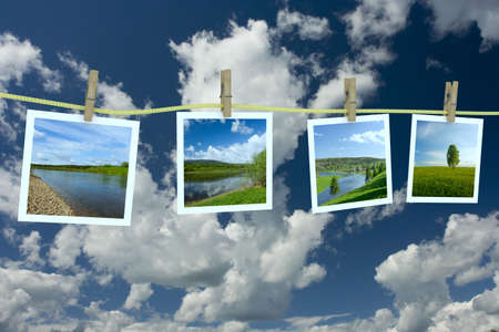 cloudscape: Landscape photographs hanging on a clothesline against a cloudscape Stock Photo