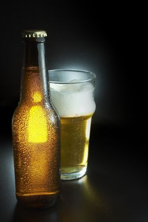 green glass bottle: Cold unopened bottle of beer near a frothy beer pint Stock Photo