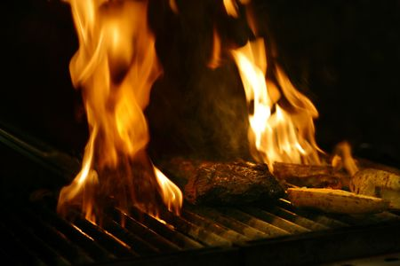 Steak cooking on wood fired flame grill in Restaurant