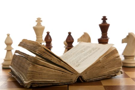 Chess composition with book on white background photo