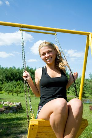 The girl on a yellow seesaw Stock Photo - 5058092