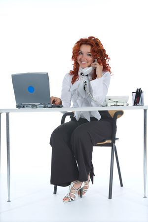 Beautiful young businesswoman calling in office photo
