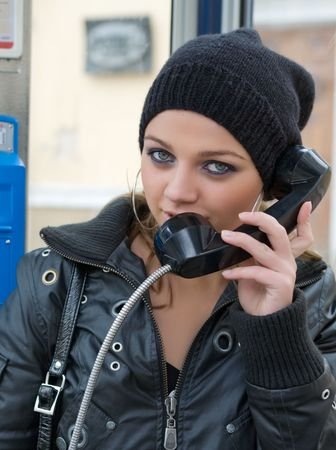 The young girl in telephone booth calling photo