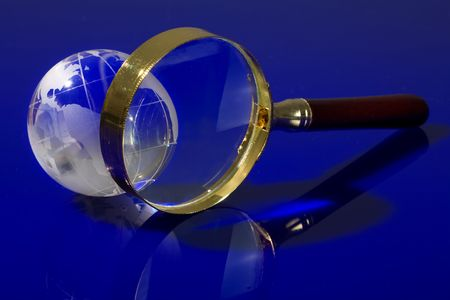 Glass globe with a magnifying glass on a blue background Stock Photo