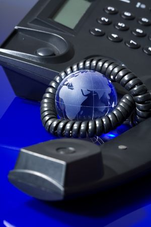 contactus:  Glass globe with phone. Global communication concept.
