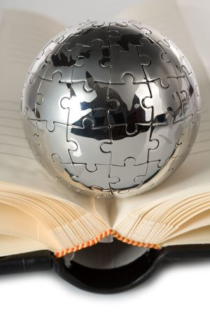 Globe puzzle with book on blue background.