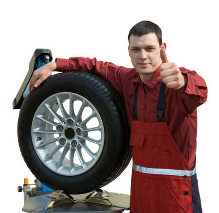 Handsome young car mechanic with wheel Stock Photo