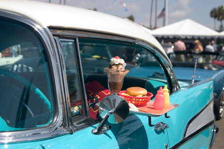 diner: Classic car with food tray attached to the drivers window. Stock Photo