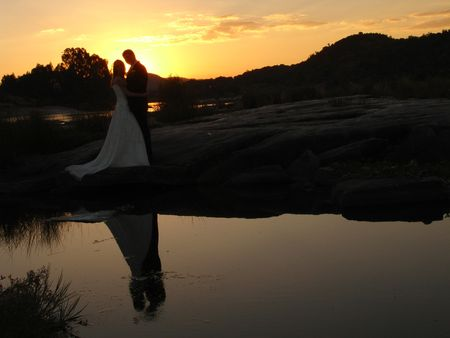 Bride and groom standing in sunset Stock Photo