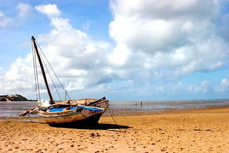 stranded: A boat stranded on the beach during low-tide in Bazaruto Stock Photo