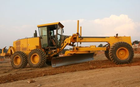 buildingsite: grader busy building and scraping a road