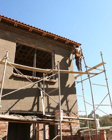 Worker plastering on scaffolding