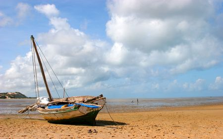fishingboat: A boat stranded on the beach during low-tide in Bazaruto Stock Photo