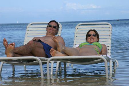Honeymoon couple sunbathing in the sea