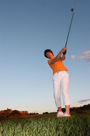 Lady golfer playing golf just before sunset