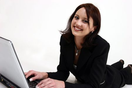 businesswoman laying on ground working on her computer